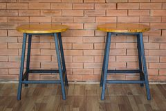 在砖墙上的两把木椅子 图库摄影