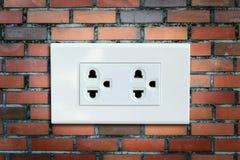在砖墙上的交流电能插座 免版税库存图片