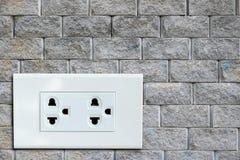在砖墙上的交流电能插座 库存图片
