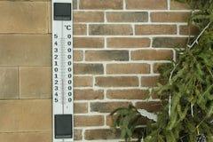 在砖墙上的大室外温度计 背景蓝色分行季节天空云杉冬天 库存图片