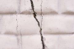在砖墙上的大宽裂缝 轻的背景 免版税库存图片