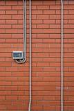 在砖墙上的电力米 库存图片