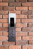 在砖墙上的电梯控制盘区 免版税图库摄影