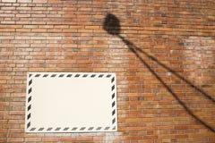 在砖墙上的白色标志有灯阴影的 库存照片