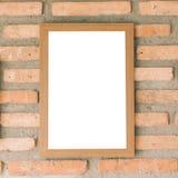 在砖墙上的空白的棕色画框 图库摄影