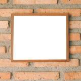 在砖墙上的空白的棕色画框 免版税库存图片