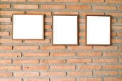 在砖墙上的空白的棕色画框 免版税库存照片