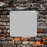 在砖墙上的空的金属标志 免版税图库摄影
