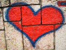 在砖墙上的红色心脏街道画 免版税库存照片