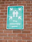 在砖墙上的绿色和白色火集合点标志 库存照片