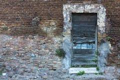 在砖墙上的老木门 左边空间 免版税图库摄影