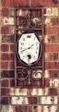 在砖墙上的老被风化的时钟 免版税库存照片