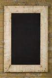 在砖墙上的葡萄酒黑板被索还的木框架 免版税图库摄影