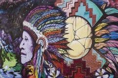 在砖墙上的街道画有印地安人的 库存照片