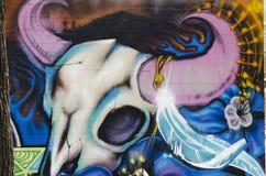 在砖墙上的街道画有母牛头骨的 免版税图库摄影