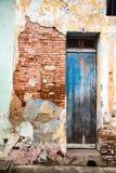 在砖墙上的被撕碎的蓝色门有残破的膏药的 免版税库存图片