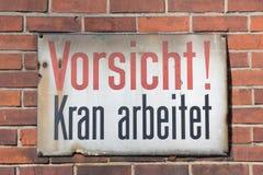 在砖墙上的Vorsicht Kran arbeitet减速火箭的标志 库存图片