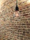 在砖墙前面的垂悬的电灯泡细丝 免版税库存图片