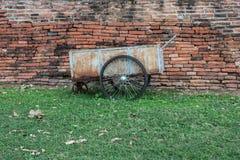 在砖墙前面的独轮车 免版税库存照片