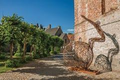 在砖墙前面的生锈的铁与树的艺术品和路在达默的晴朗的蓝天下 免版税库存照片