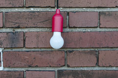 在砖墙前面的电灯泡 库存图片
