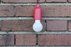 在砖墙前面的电灯泡 免版税库存图片