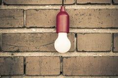 在砖墙前面的电灯泡 免版税图库摄影