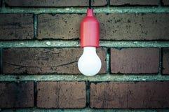 在砖墙前面的电灯泡 免版税库存照片