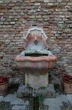 在砖墙前面的老喷泉 免版税库存图片