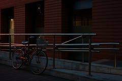 在砖墙前面的金属篱芭附近停放的都市自行车 图库摄影