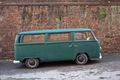 在砖墙前面的绿色大众搬运车 免版税库存照片