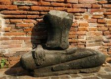 在砖墙旁边的一个老无首的菩萨雕象 免版税库存照片