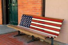 在砖墙旁边的老,被风化的美国长凳 库存照片