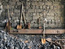 在砖墙旁边的铁锹在煤电植物中 库存图片
