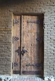 在砖墙的古老木门 库存照片