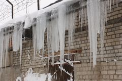 在砖墙的垂悬的冰柱 免版税库存图片