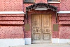 在砖墙的大老木门 免版税图库摄影