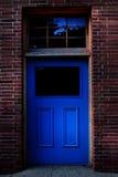 在砖墙的深蓝门 免版税库存图片