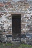 在砖墙的老木门 免版税库存图片