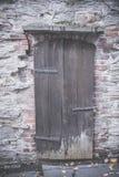 在砖墙的老木门 库存图片