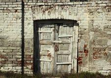 在砖墙的老被风化的木门 图库摄影