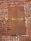 在砖墙的老金属门 免版税图库摄影
