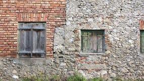 在砖墙的被风化的木快门 免版税库存照片