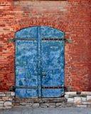 在砖墙的被风化的老门 免版税图库摄影