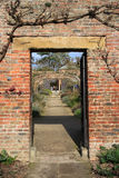 在砖墙的门户在村庄庭院里 免版税库存图片