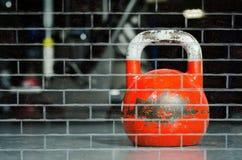 在砖墙背景影响绘的健身房地板上的红色kettlebell 免版税库存图片