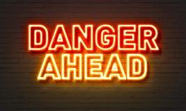 在砖墙背景的前面危险霓虹灯广告 免版税库存图片