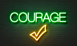 在砖墙背景的勇气霓虹灯广告 库存照片