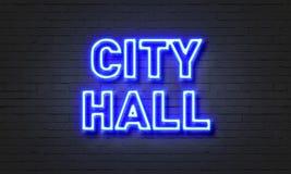 在砖墙背景的市政厅霓虹灯广告 图库摄影