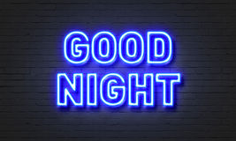 在砖墙背景的晚上好霓虹灯广告 免版税库存图片